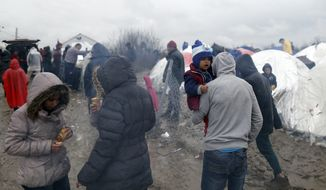 Migrants walk in the mud in an improvised camp on the border line between Macedonia and Serbia near the northern Macedonian village of Tabanovce, Friday, March 11, 2016. About 1,500 refugees remain stranded at the Macedonian border with Serbia as the borders on the Balkan migrant route are closing.  (AP Photo/Darko Vojinovic)