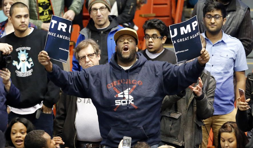 A protester holds up a ripped campaign sign for Republican presidential candidate Donald Trump before a rally on the campus of the University of Illinois-Chicago, Friday, March 11, 2016, in Chicago. (AP Photo/Charles Rex Arbogast)