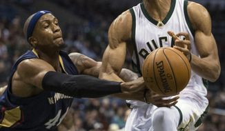 Milwaukee Bucks' Giannis Antetokounmpo is fouled by New Orleans Pelicans' Dante Cunningham during the second half of an NBA basketball game Saturday, March 12, 2016, in Milwaukee. (AP Photo/Tom Lynn)