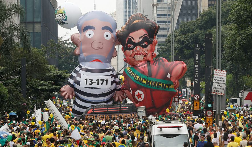 """Demonstrators in Sao Paulo parade inflatable dolls depicting former Brazilian President Luiz Inacio Lula da Silva in prison garb and current President Dilma Rousseff dressed as a thief, with a presidential sash that reads """"Impeachment."""" (Associated Press)"""