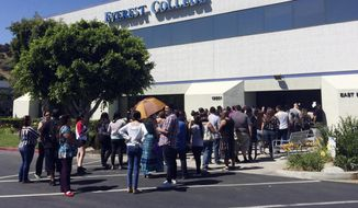 FILE - In this April 28, 2015, file photo, students wait outside Everest College in Industry, Calif., hoping to get their transcriptions and information on loan forgiveness and transferring credits to other schools. Despite pledging to distance itself from the poor business practices of the for-profit Corinthian Colleges Inc, the new owner of the Everest career college chain has retained key members of its staff and some of its hard-charging sales tactics. (AP Photo/Christine Armario, File)