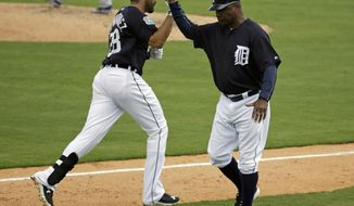 Detroit Tigers' J.D. Martinez, left, gets a high five from third base coach Dave Clark after he hit a home run in the fifth inning in a spring training baseball game, Monday, March 14, 2016, in Lakeland, Fla. (AP Photo/John Raoux)