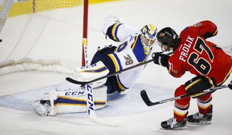 St. Louis Blues goalie Anders Nilsson, left, of Sweden, lets in a goal from Calgary Flames' Michael Frolik, of the Czech Republic, during the third period of an NHL hockey game in Calgary, Alberta, Monday, March 14, 2016. (Jeff McIntosh/The Canadian Press via AP) MANDATORY CREDIT