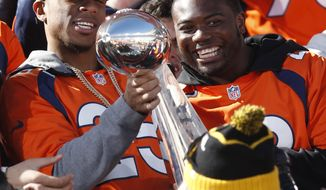 FILE - In this Tuesday, Feb. 9, 2016, file photograph, Denver Broncos cornerback Chris Harris, left, holds the Lombardi Trophy as running back C.J. Anderson looks on at a rally following a parade through downtown Tuesday, Feb. 9, 2016 in Denver. The Broncos will keep Anderson on the roster after matching Miami's four-year, $18-million offer to the running back who scored the Broncos' only offensive touchdown in Denver's victory over Carolina in Super Bowl 50. (AP Photo/David Zalubowski, file)