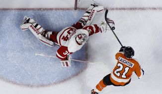 Detroit Red Wings' Petr Mrazek, left, blocks a shot by Philadelphia Flyers' Scott Laughton during the second period of an NHL hockey game, Tuesday, March 15, 2016, in Philadelphia. (AP Photo/Matt Slocum)