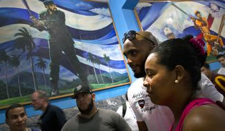 Professional Cuban-born baseball player Alexei Ramirez, second from right, who used to play with the Chicago White Sox, poses for a photo with a fan before giving a baseball clinic to children in Havana, Cuba, Wednesday, Dec. 16, 2015. A group of Cuban-born baseball stars once disdained by the island's government for defecting to the United States taught their craft to some of the island's youngest players on Wednesday as part of a triumphant return to Cuba. Behind hangs a painting of Fidel Castro playing baseball. (AP Photo/Ramon Espinosa)