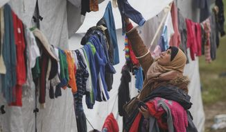 A woman hangs clothing to dry at the northern Greek border point of Idomeni, Greece, Thursday, March 17, 2016. Leaders of the EU's 28 divided nations plan to reconvene in Brussels this week in hopes of ironing out disagreements on a proposed agreement with Turkey in the migrants crisis. (AP Photo/Vadim Ghirda)