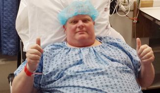 In this Monday, May 11, 2015, file photo provided by Dan Jacobs, former Toronto Mayor Rob Ford gives a thumbs up before surgery in Toronto, to remove a cancerous tumor from his abdomen. On Thursday, March 17, 2016, Ford's chief of staff, Jacobs, said doctors are working on building his strength to be able to resume chemotherapy. (Courtesy Dan Jacobs via AP)
