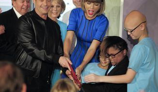 Television personality and producer Ryan Seacrest, foreground left, and singer Taylor Swift, center, join young patients at a ribbon cutting ceremony for the new Seacrest Studio, Friday, March 18, 2016, at Monroe Carell Jr. Children's Hospital at Vanderbilt in Nashville, Tenn. The fully functioning studio allows patients to record, do interviews, play songs and broadcast to the rooms in the hospital. (George Walker/The Tennessean via AP)
