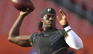 FILE - In this Thursday, Aug. 13, 2015 file photo, Washington Redskins quarterback Robert Griffin III warms up before the Redskins play the Cleveland Browns in an NFL preseason football game in Cleveland. Free agent quarterback Robert Griffin III visited the Browns, Saturday, March 19, 2016.  Griffin, who was released earlier this month by Washington, met with coach Hue Jackson and others on Saturday, said the person who spoke to the Associated Press on condition of anonymity because the team is not disclosing its plans during free agency.(AP Photo/Ron Schwane, File)