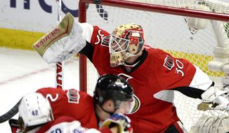 The puck passes over the crossbar after a save by Ottawa Senators' goalie Andrew Hammond (30) against the Montreal Canadiens during the first period of an NHL hockey game Saturday, March 19, 2016, in Ottawa, Ontario. (Justin Tang/The Canadian Press via AP)