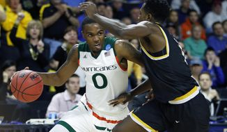Miami's Ja'Quan Newton (0) drives past Wichita State's Zach Brown during the first half of a second round game in the NCAA men's college basketball tournament in Providence, R.I., Saturday, March 19, 2016. (AP Photo/Michael Dwyer)
