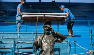 Workers prepare for Tuesday's friendly game between the Tampa Rays and the Cuban national team at the Latinoamericano stadium in Havana. (Associated Press)