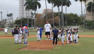 Tampa Bay Rays pitching coach Jim Hickey instructs a local team of 9- and 10-year-olds on pitching mechanics during a drill at Desa Field, near the Plaza de la Revolucion in Havana on Monday. (Zac Boyer/The Washington Times)