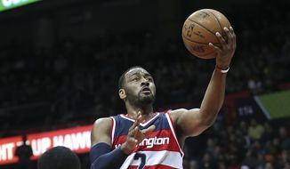 Washington Wizards guard John Wall (2) goes in for a basket against Atlanta Hawks guard Tim Hardaway Jr. (10) in the second half of an NBA basketball game, Monday, March 21, 2016, in Atlanta. (AP Photo/John Bazemore)