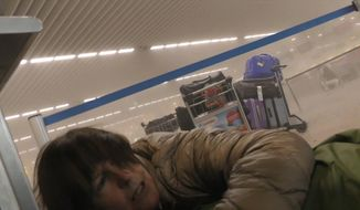 In this photo provided by Ralph Usbeck an unidentified traveller lies on the ground in a smoke filled terminal at Brussels Airport, in Brussels, after explosions Tuesday, March 22, 2016. Authorities locked down the Belgian capital on Tuesday after explosions rocked the Brussels airport and subway system, killing  a number of people and injuring many more. Belgium raised its terror alert to its highest level, diverting arriving planes and trains and ordering people to stay where they were. Airports across Europe tightened security.  (Ralph Usbeck via AP)