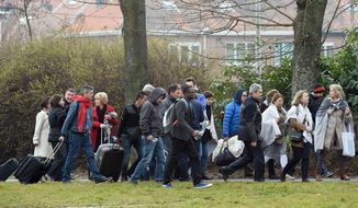 People walk across a field as they are evacuated from Zaventem Airport in Brussels after an explosion on Tuesday, March 22, 2016. Explosions, at least one likely caused by a suicide bomber, rocked the Brussels airport and subway system Tuesday, prompting a lockdown of the Belgian capital and heightened security across Europe. At least 26 people were reported dead. (AP Photo/Geert Vanden Wijngaert)