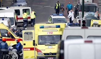 Emergency services evacuate a victim wrapped in a blanket after a explosion in a main metro station in Brussels on Tuesday, March 22, 2016. Explosions rocked the Brussels airport and the subway system Tuesday, killing at least 13 people and injuring many others just days after the main suspect in the November Paris attacks was arrested in the city, police said. (AP Photo/Virginia Mayo)