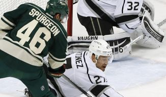 A pass gets by Minnesota Wild's Jared Spurgeon, left, as Los Angeles Kings' Alec Martinez and goalie Jonathan Quick defend the net in the first period of an NHL hockey game Tuesday, March 22, 2016, in St. Paul, Minn. (AP Photo/Jim Mone)
