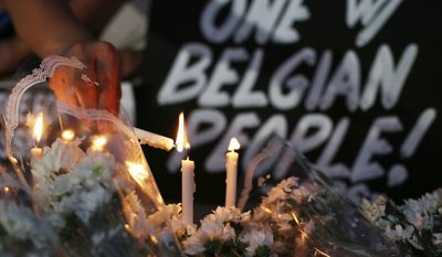A Filipino activist lights candles among flowers offered for victims of Brussels attacks beside a condolence sign in the suburban north of Manila, Philippines.
