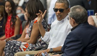 President Barack Obama, center, talks with Cuban President Raul Castro, right, as they attend an exhibition baseball game between the Tampa Bay Rays and the Cuban National team at the Estadio Latinoamericano, Tuesday, March 22, 2016, in Havana, Cuba. Also attending are members of the first family from l-r, Malia Obama, Sasha Obama and first lady Michelle Obama. (AP Photo/Pablo Martinez Monsivais)