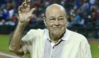FILE - In this April 14, 2013, file photo, Arizona Diamondbacks broadcaster Joe Garagiola, center, waves to a cheering crowd during festivities honoring the retiring broadcaster, prior to a baseball game against the Los Angeles Dodgers, in Phoenix. Former big league catcher and popular broadcaster Joe Garagiola has died. He was 90. The Arizona Diamondbacks say Garagiola died Wednesday, March 23, 2016. He had been in ill health in recent years. (AP Photo/Ross D. Franklin, File)