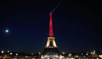 The Eiffel Tower is illuminated with the Belgium national colors black, yellow and red in honor of the victims of the today's attacks at the airport and the metro station in Brussels, in Paris, Tuesday, March 22, 2016. Explosions, at least one likely caused by a suicide bomber, rocked the Brussels airport and its subway system Tuesday, prompting a lockdown of the Belgian capital and heightened security across Europe. (AP Photo/Thibault Camus)