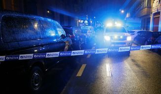 Police guard a checkpoint during a raid in the suburb of Schaerbeek in Brussels early Friday. Six people were detained in late-night raids Thursday across the Belgian capital. (Associated Press)