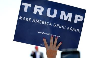 In this March 19, 2016 file photo, a supporter holds a sign as Republican presidential candidate Donald Trump speaks during a campaign rally in Fountain Hills, Ariz. (AP Photo/Matt York, File)