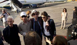 Members of The Rolling Stones, from left, Charlie Watts, Mick Jagger, Keith Richards and Ron Wood talk to journalists upon their arrival to Jose Marti international airport in Havana, Cuba, Thursday, March 24, 2016. The Stones are performing a free concert in Havana on Friday, becoming the most famous act to play Cuba since its 1959 revolution. (AP Photo/Ramon Espinosa)
