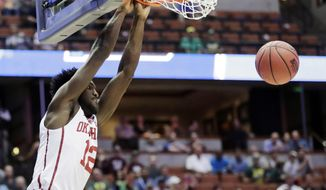 Oklahoma forward Khadeem Lattin dunks as Texas A&M center Tyler Davis looks on during the first half of an NCAA college basketball game in the regional semifinals of the NCAA Tournament, Thursday, March 24, 2016, in Anaheim, Calif. (AP Photo/Gregory Bull)