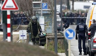 A member of emergency services wearing protective clothing investigates the scene in Schaerbeek, Belgium, Friday March 25, 2016. (AP Photo/Alastair Grant)