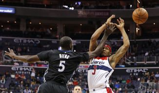Minnesota Timberwolves center Gorgui Dieng (5) fouls Washington Wizards guard Bradley Beal during the second overtime of an NBA basketball game Friday, March 25, 2016, in Washington. The Timberwolves won 132-129. (AP Photo/Alex Brandon)