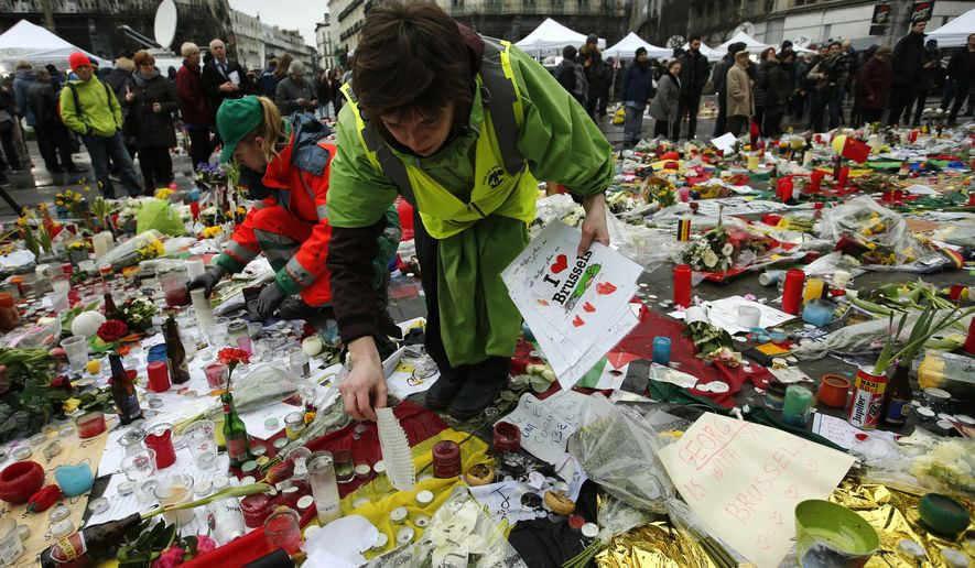 Workers from the City of Brussels collect some of the tributes to preserve them at one of the memorial sites, after the recent attacks in the capital at the Place de la Bourse in Brussels, Friday, March, 25, 2016. (AP Photo/Alastair Grant)