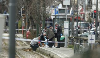 Investigators collect evidence near a tram track in Schaerbeek, Belgium, Friday March 25, 2016. (AP Photo/Alastair Grant)