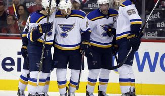St. Louis Blues defenseman Kevin Shattenkirk (22), center Kyle Brodziak (28), center David Backes (42) and defenseman Colton Parayko (55) celebrate a goal by Brodziak in the second period of an NHL hockey game against the Washington Capitals, Saturday, March 26, 2016, in Washington. (AP Photo/Alex Brandon)
