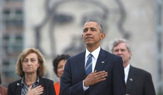 """Backdropped by a monument depicting Cuba's revolutionary hero Ernesto """"Che"""" Guevara, U.S. President Barack Obama listens to the U.S. national anthem during a ceremony at the Jose Marti Monument in Havana, Cuba, Monday, March 21, 2016. (AP Photo/Dennis Rivera)"""