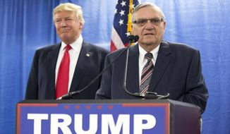 FILE - In this Jan. 26, 2016 file photo, Republican presidential candidate Donald Trump, left, is joined by Maricopa County, Ariz., Sheriff Joe Arpaio during a new conference in Marshalltown, Iowa. Arizona's presidential primary marked a return to the political spotlight for Arpaio, an influential figure in Republican circles on immigration enforcement who has spent the last year lying low as he faces the possibility of criminal charges. His endorsement of Republican front-runner Donald Trump led to a round of TV interviews and appearances with the candidate, including a rally in Arpaio's hometown.(AP Photo/Mary Altaffer, File)
