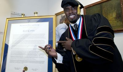 Entertainer and entrepreneur Sean Combs poses next to his honorary degree of Doctor of Humanities during the graduation ceremony at Howard University in Washington, on Saturday, May 10, 2014.( AP Photo/Jose Luis Magana)
