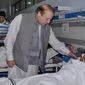 In this photo released by Press Information Department, Pakistan's Prime Minister Nawaz Sharif talks to an injured victim of Sunday's suicide bombing during his visit to a local hospital in Lahore, Pakistan, Monday, March 28, 2016. Pakistan's prime minister on Monday vowed to eliminate perpetrators of terror attacks such as the massive suicide bombing that targeted Christians gathered for Easter the previous day in the eastern city of Lahore, killing 70 people. (AP Photo/Press Information Department via AP)