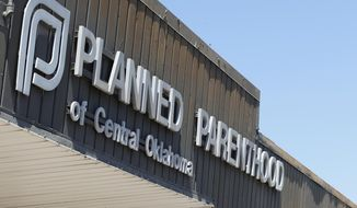 This July 24, 2015, photo shows a sign at a Planned Parenthood Clinic in Oklahoma City. Though congressional Republicans' bid to defund Planned Parenthood was vetoed by President Barack Obama, anti-abortion activists and politicians are achieving a growing portion of their goal with an aggressive state-by-state strategy. Over the past year, more than a dozen states have sought to halt or reduce public funding for Planned Parenthood.  (AP Photo/Sue Ogrocki, File)