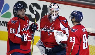 Washington Capitals goalie Braden Holtby, center, celebrates with defenseman Nate Schmidt (88) and center Jay Beagle (83) after an NHL hockey game against the Columbus Blue Jackets, Monday, March 28, 2016, in Washington. The Capitals won 4-1. (AP Photo/Alex Brandon)