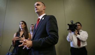 In this photo taken Aug. 25, 2015, Republican presidential candidate Donald Trump's campaign manager Corey Lewandowski watches as Trump speaks in Dubuque, Iowa. Florida police have charged Lewandowski with simple battery in connection with an incident earlier in the month involving a reporter. (AP Photo/Charlie Neibergall)