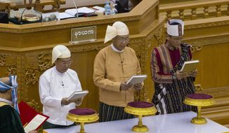 Lawmakers from right, Henry Van Hti Yu as seconnd vice president, Htin Kyaw as president and Myint Swe as first-vice president, take oaths during a ceremony in parliament in Naypyitaw, Myanmar, Wednesday, March 30, 2016. Htin Kyaw, a trusted friend of Nobel laureate Aung San Suu Kyi took over as Myanmar's president Wednesday, taking a momentous step in the country's long-drawn transition toward democracy after more than a half-century of direct and indirect military rule. (AP Photo/Gemunu Amarasinghe)