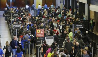In this March 17, 2016, photo, travelers wait in line for security screening at Seattle-Tacoma International Airport in Seattle. Fliers will likely face massive security lines at airports across the country this summer, with airlines already warning passengers to arrive at least two hours early or risk missing their flight. (AP Photo/Ted S. Warren)