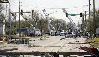 Utility crews work to fix broken power lines and poles at 46th Street North and North Hartford Avenue after a tornado moved through the area the previous night, taken in Tulsa, Okla., Thursday, March 31, 2016. (James Gibbard/Tulsa World via AP)