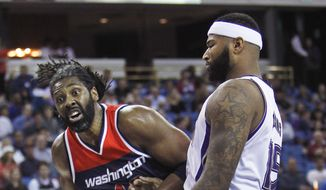 Washington Wizards forward Nene (42) battles for position under the basket against Sacramento Kings center DeMarcus Cousins (15) during the first half of an NBA basketball game in Sacramento, Calif., Wednesday, March. 30, 2016. (AP Photo/Steve Yeater)