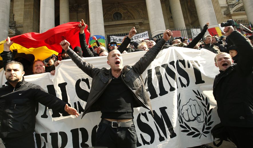 """FILE - In this Sunday, March, 27, 2016 file photo, right-wing demonstrators chant slogans next to one of the memorials to the victims of the recent Brussels attacks, at the Place de la Bourse in Brussels. As extreme-right groups threaten to take Molenbeek neighborhood by storm Saturday, April 2, community leaders fear its predominantly Muslim young people will fight back. """"They don't trust the police and they aren't going to take it,"""" said Fouad Ben Abdelkader, a teacher in the neighborhood. On Thursday he joined a meeting of a couple dozen community leaders and mentors to neighborhood youths who feel adrift in mainstream Belgian society. The group of community organizers was looking for ways to head off an escalation of violence in the largely Muslim neighborhood, hoping to avoid a situation like occurred last Sunday when hundreds of black-clad hooligans shouting Nazi slogans disrupted a memorial at Brussels' Bourse square for the 32 victims of the March 22 attacks on the airport and subway system. (AP Photo/Alastair Grant, file)"""