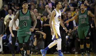 Boston Celtics' Isaiah Thomas (4) and Evan Turner (11) celebrate as time expires, and Golden State Warriors' Shaun Livingston (34) walks off the court at the end of an NBA basketball game Friday, April 1, 2016, in Oakland, Calif. Boston won 109-106. (AP Photo/Marcio Jose Sanchez)