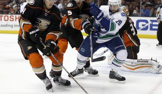 Anaheim Ducks defenseman Cam Fowler, left, controls the puck as defenseman Korbinian Holzer, center, of Germany, controls Vancouver Canucks left wing Chris Higgins, right, during the first period of an NHL hockey game in Anaheim, Calif., Friday, April 1, 2016. (AP Photo/Alex Gallardo)